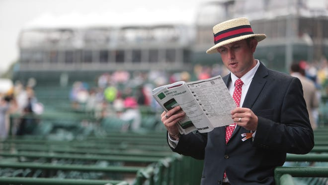 Josh Dvorak of Prairie Dusk, Wis., takes a glance at the race program during the 144th running of the Kentucky Derby on Saturday, May 5, 2018, at Churchill Downs in Louisville, Kentucky.