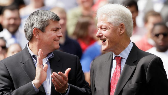 In this Oct. 6, 2014 file photo, Arkansas Democratic gubernatorial candidate Mike Ross, left, applauds former President Bill Clinton during a political rally at the University of Central Arkansas in Conway, Ark.