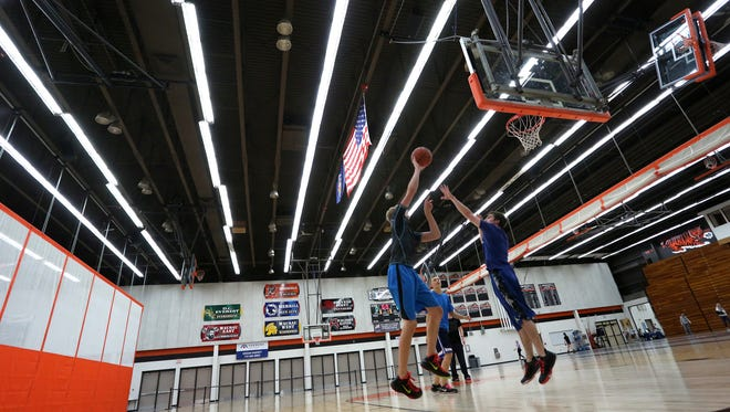 A group of boys play basketball in a phy-ed class in the Boson Company Fieldhouse at Marshfield High School, Thursday, October 22, 2015. The Boson Company of Marshfield, for the third consecutive year, has purchased the naming rights to the facility.