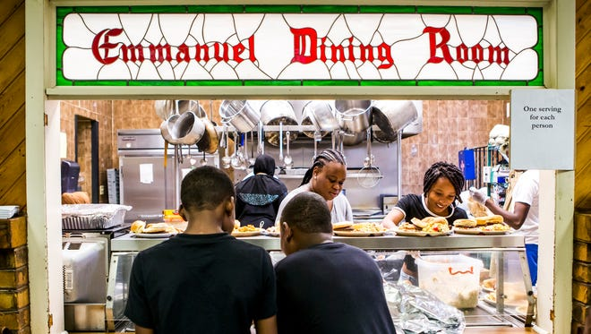 Humbled Helping Hands volunteers prepare meals for dozens of Wilmington residents at the Emmanuel Dining Room in Wilmington on Sunday afternoon.