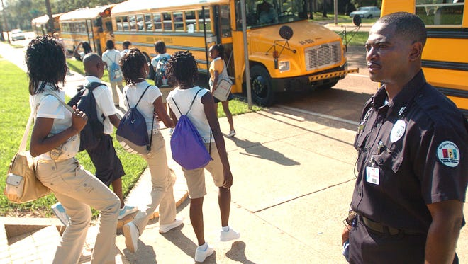 A Jackson Public Schools Security Guard watches as students head to waiting buses for rides back to their Middle Schools after a morning at Power APAC. The district has come under scrutiny from state oversight officials because of issues with transportation and other accrediting standards related to discipline, order and safety.