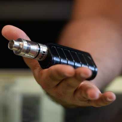 Basit Memon, owner of Aladdin Smoke Shop, holds a Tesla