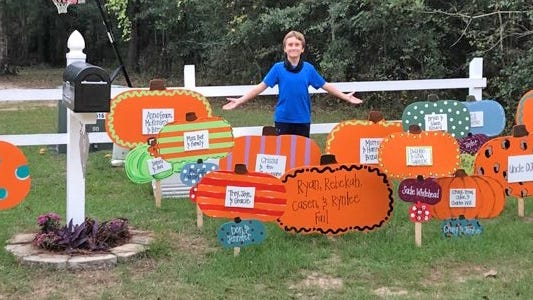 Noah Hutson stands beside some of the 125 colorful pumpkins in the pumpkin patch set up in his front yard. Paidan Productions sold pumpkins to people as a fundraiser to help Hutson and his family financially as he battles a brain tumor.