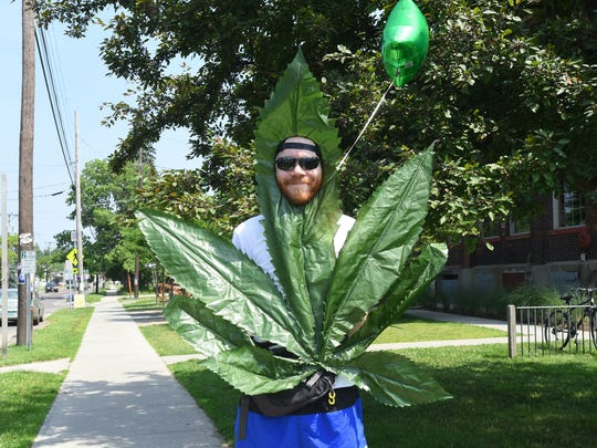 Brandon Allen, of Burlington, stands on Pine Street in Burlington on Sunday, July 1, 2018 dressed as a marijuana leaf waving in customers to Green State Gardener, a shop that supplies growing equipment. Recreational marijuana became legal in Vermont on July 1, 2018.