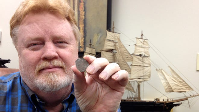 """Buz Anderson with Spanish coin from El Cazador. That's a model of the spice trader """"Cutty Sark"""" in background, a gift to Paul Doerle from McCormick."""