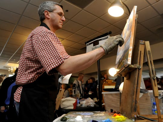 David Mensing works the paint on his canvas during