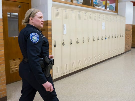 Port Huron Police school resource officer Laura Phillips walks through the hallways at Port Huron High School while students are in class March 8.