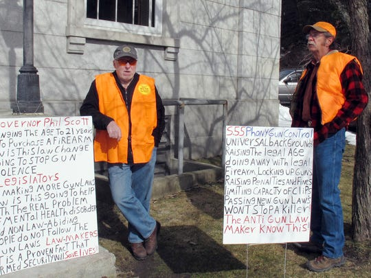 "Bert Saldi, left, of Barre, stands with another protester who wouldn't give his name, outside the Vermont Statehouse on Tuesday March 27, 2018, in Montpelier. They were at the Statehouse where The House was set to debate a measure that would raise the legal age for gun purchases, expand background checks and ban high-capacity magazines and rapid-fire devices known as ""bump stocks."" Opponents said the legislation is unconstitutional and won't enhance school safety. (AP Photo/Wilson Ring)"