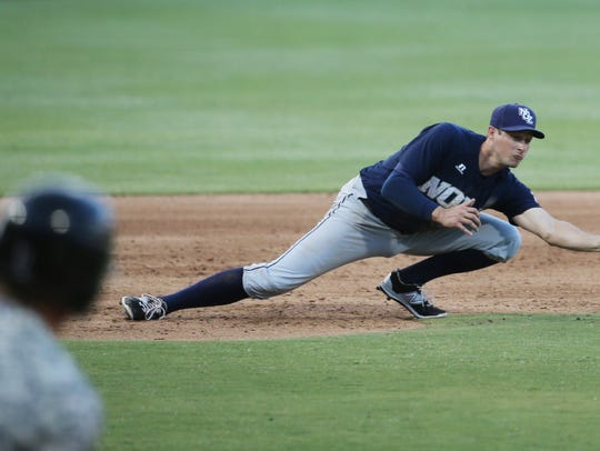 New Orleans third baseman Don Kelly reaches to catch