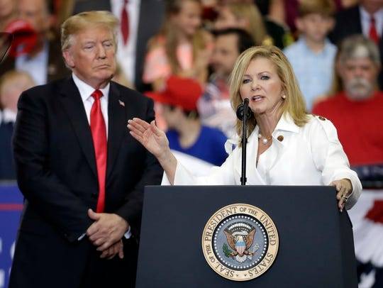 President Donald Trump listens as U.S. Rep. Marsha