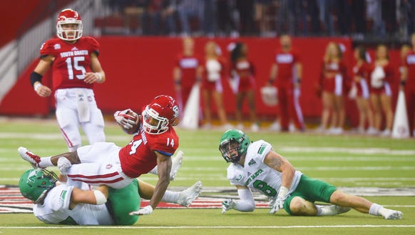USD's  Michael Fredrick is tackled by UND defense during