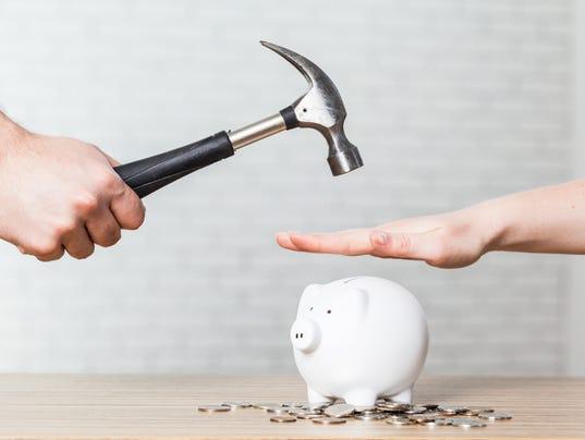 hammer raised above a white piggy bank