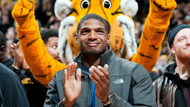 In this Feb. 15, 2014, file photo, Missouri's All-American defensive end Michael Sam claps during the Cotton Bowl trophy presentation at halftime of a college basketball game between Missouri and Tennessee in Columbia.