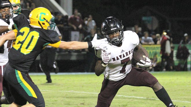 Navarre's Michael Carter looks to turn the corner against Catholic's Colin Acromite during the Raiders' win Friday night.