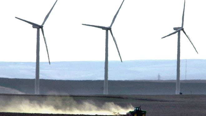 Vestas wind turbines tower over a tractor and plow tilling farmland near Wasco, Ore., in this photo from 2002.