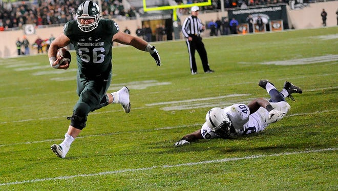 Center Jack Allen (66) gets around a Penn State defender on his way to a nine-yard touchdown run in the second half of MSU's 55-16 win over Penn State Saturday, November 28, 2015, at Spartan Stadium in East Lansing.