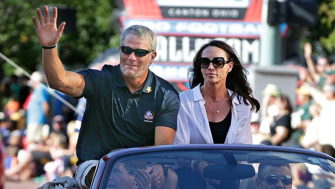 Hall of Fame inductee Brett Favre and his wife Deanna Favre wave to the crowd along the parade route during the Canton Repository Grand Parade as part of the NFL Pro Football Hall of Fame Enshrinement Festival.