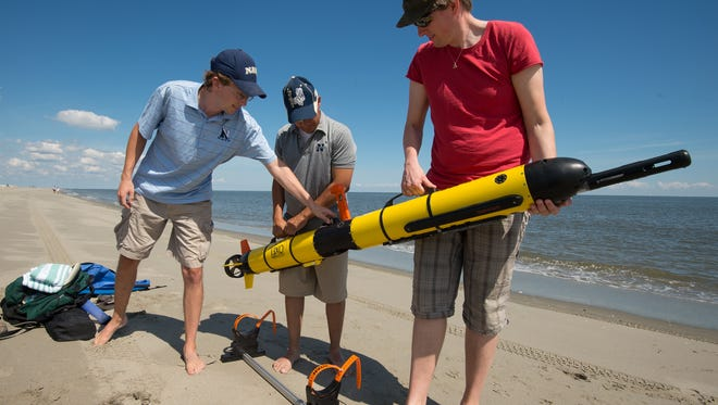 Lab manager Andrew Keppel, left, Luis Rodriguez, lab technician with the Naval Academy and Tor Inge Loenmo, an exchange student from University of Oslo Norway to the University of New Hampshire, prepare their autonomous underwater vehicle to test water quality and map the bottom off Broadkill Beach.