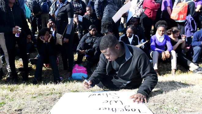 Haywood High School senior Malik Green creates a sign outside of his school Dec. 4 as he and other students walked outside in protest of punishment over alleged threats posted on social media.