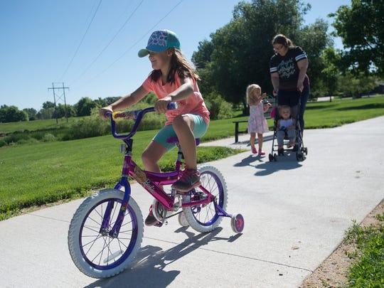Jocelyn Jerke, 5, rides her bike ahead of her mother,