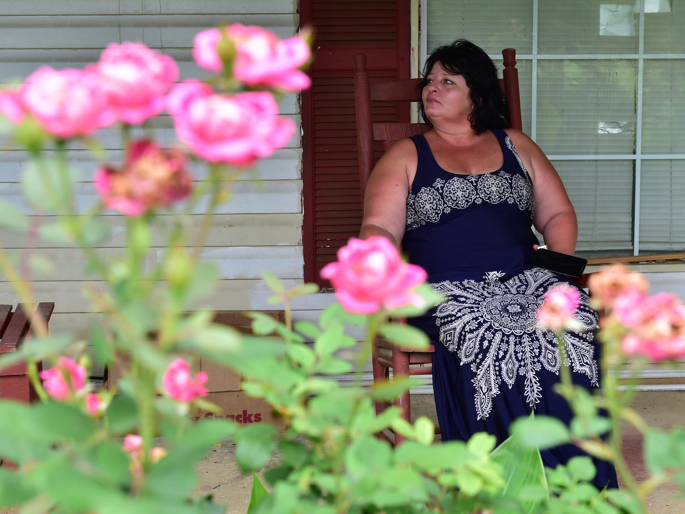 Marty Jean Pettit sits in a rocking chair on the porch of the Mantachie house where she's living temporarily. She has been struggling to access services for herself and her son, who has a mental illness.