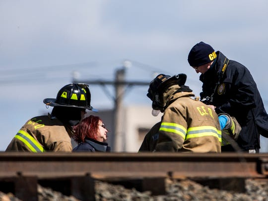 Local officials work at over the remains of one of two people killed after an Amtrak train struck a piece of construction equipment on the tracks in Chester, Pa. on Sunday morning.