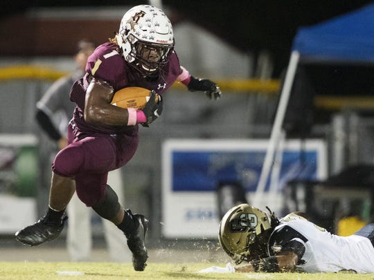 Riverdale High School's Quantavius Brown eludes Golden Gate defenders on Friday at Riverdale High School in Fort Myers. Riverdale beat Golden Gate 41-10. It was also Senior Night for Riverdale players, cheerleaders and band members.