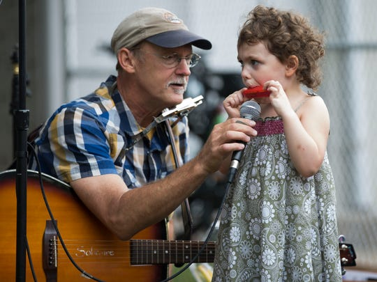 """Sylvia Buente, 3, plays the harmonica as Art """"The Dud""""' Woodward holds the microphone for the surrounding audience to hear during Parksfest earlier in the year."""