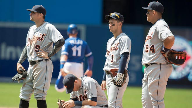 Tigers infielders wait out yet another pitching change in the seventh inning of the game against the Blue Jays in Toronto Sunday.