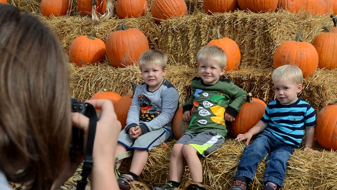 Twins Justin (left) and Jason Barber and Daniel Wedge get their photo taken at the pyramid of pumpkins at last year's Pumpkinfest. This year's festival opens Friday.