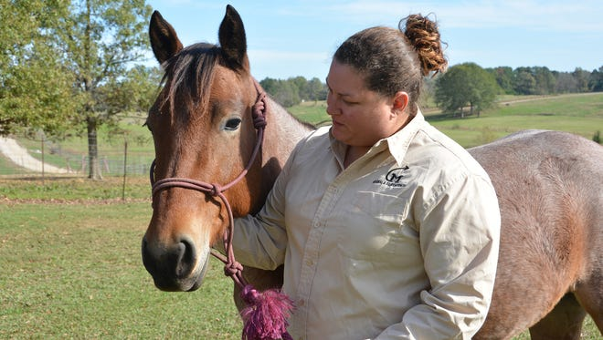 Jamie Burkhardt Speed, an agricultural technician with the Mississippi State University Department of Animal and Dairy Sciences, holds a 2-year-old mare that is for sale in the online auction underway until Nov. 21.