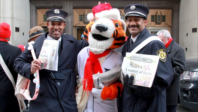 PAWS, the Detroit Tigers mascot, is photographed with Lt. Dale Bradley, left and Capt. Gerod Funderburg during the Goodfellows sale in 2014. Both men are Goodfellows members and work in the Community Relations Department of the Detroit Fire Department.