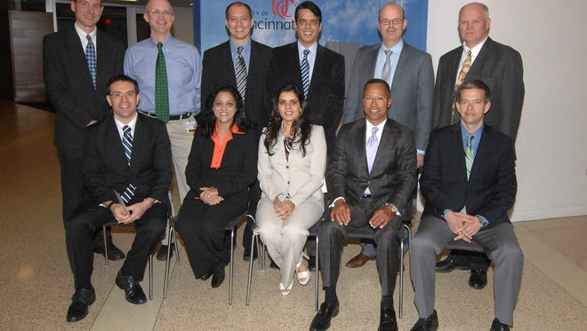 Thirteen University of Cincinnati College of Medicine professors were honored last week for receiving the Patient Experience Excellence Award. First row (from left): Drs. Adam Ingraffea, Sona Sharma, Nadia Yaqub, Hugh Gloster and Michael Holliday, Back row: Drs. Andrew Duker, Bradley Mathis, Michael Canos, William Ball, dean of the College of Medicine; Dr. Richard Lofgren, president and chief executive officer of UC Health; Dr. Myles Pensak, senior associate dean for health affairs; Abid Yaqub, Lee Zimmer and Stephen Dailey.