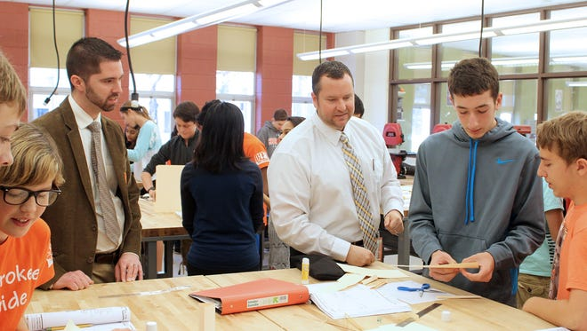 Cherokee High School students in a Project Lead The Way classroom are paid a visit by BAE Systems engineers after the company's $7,500 grant.