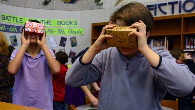 Poplar Grove Middle School students Daniel Morra, left, and William Walker virtually explore a coral reef in the Galapagos Islands using Google Expeditions.