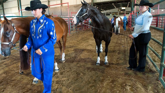 Contestants wait with their horses in a barn during the LSU AgCenter State Horse Show at the Lamar Dixon Expo Center on July 12, 2016.