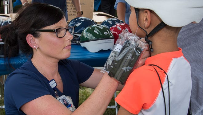 Children and their parents learned the proper way to select and wear a bicycle helmet, and many received free helmets. Lindsey Galati, RN, fits 6-year-old James Koch of Westland with a new bike helmet.