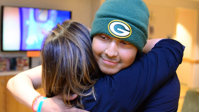 Thomas Harris hugs RN Ashley Hain of the Children's Hospital of Wisconsin at his bell ringing ceremony.