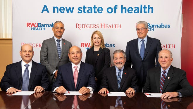 Seated, from left: RWJBarnabas Health Board of Trustees Chairman Jack Morris, RWJBarnabas Health President and CEO Barry Ostrowsky, Rutgers Biomedical and Health Sciences (RBHS) Chancellor Brian Strom, Rutgers University President Robert Barchi. Standing, from left: RBHS Senior Vice Chancellor for Clinical Affairs Vicente Gracias, RBHS Senior Vice Chancellor for Finance and Administration Kathleen Bramwell, RWJBarnabas Health Board of Trustees Vice Chairman Marc Berson.
