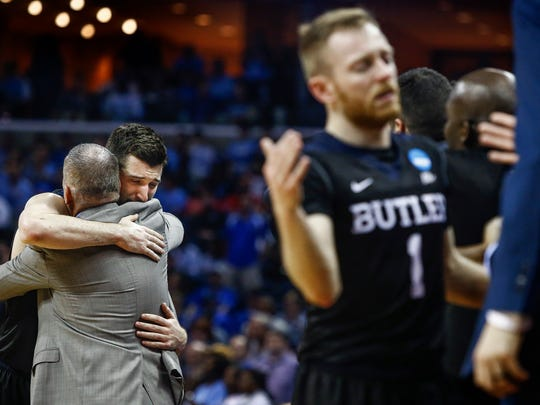 Butler University senior Andrew Chrabascz (middle left) hugs head coach Chris Holtmann (left) during the final minute of a 92-80 loss to University of North Carolina in their NCAA tournament Sweet Sixteen matchup at the FedExForum.