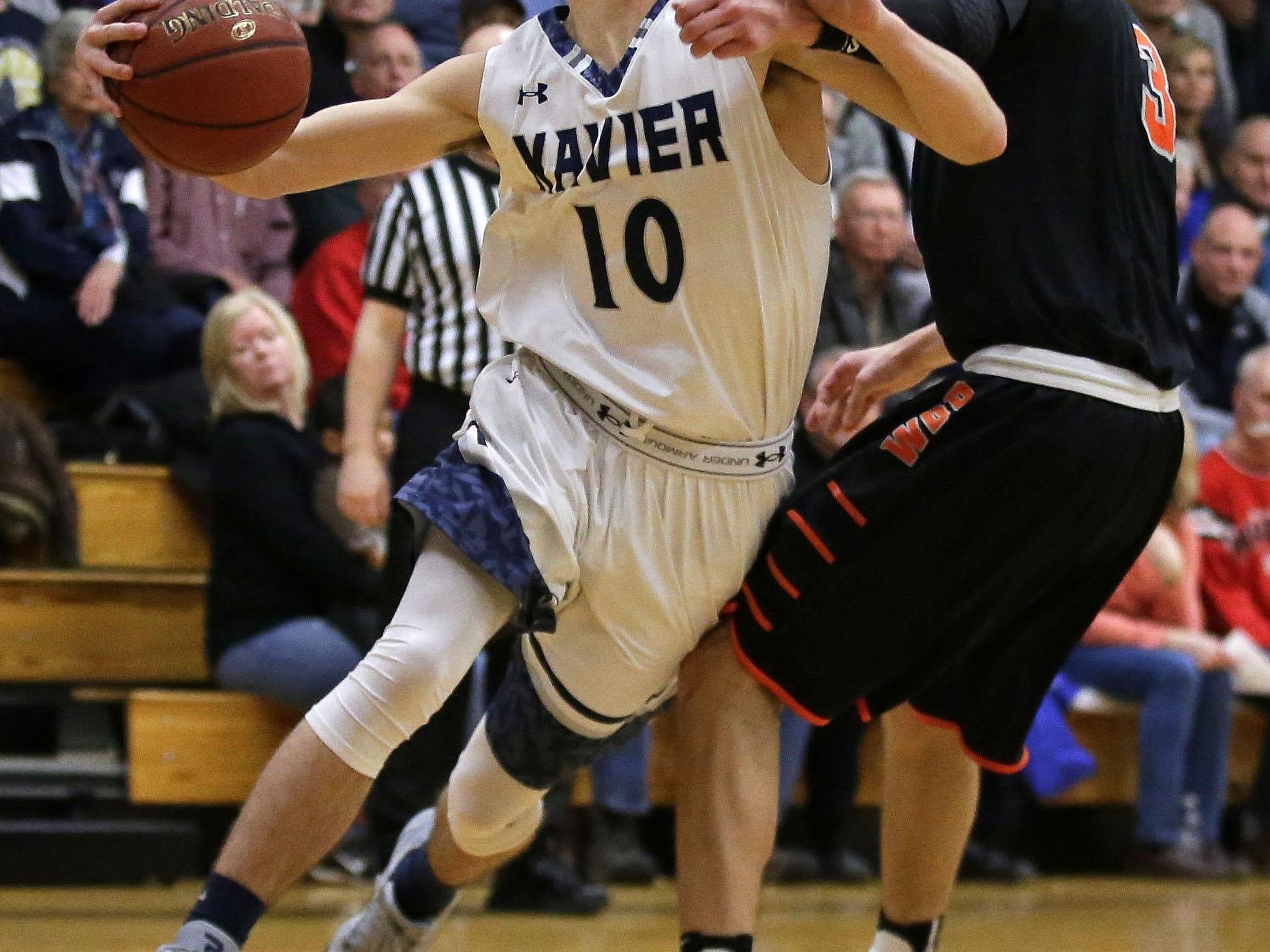 Xavier's Cal Christensen drives to the basket against Tyler Schwartz of West De Pere.