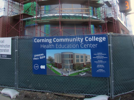 A sign on the fence around the construction site of the new Corning Community College health education center shows what the finished facility will look like.
