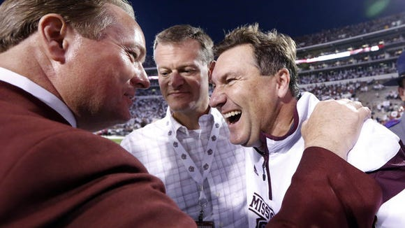 Mississippi State President Mark Keenum (left), athletic director Scott Stricklin (center) and Dan Mullen celebrate after MSU's win against Kentucky last season.