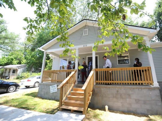 Attendees for a dedication ceremony mill on the front porch of Nikecia White's new home in Knoxville on Thursday, June 23, 2016. Habitat for Humanity and Home Federal Bank employees gathered White, a caregiver for adults with intellectual disabilities at Sertoma Center, and her family members to celebrate the occasion. (ADAM LAU/NEWS SENTINEL)