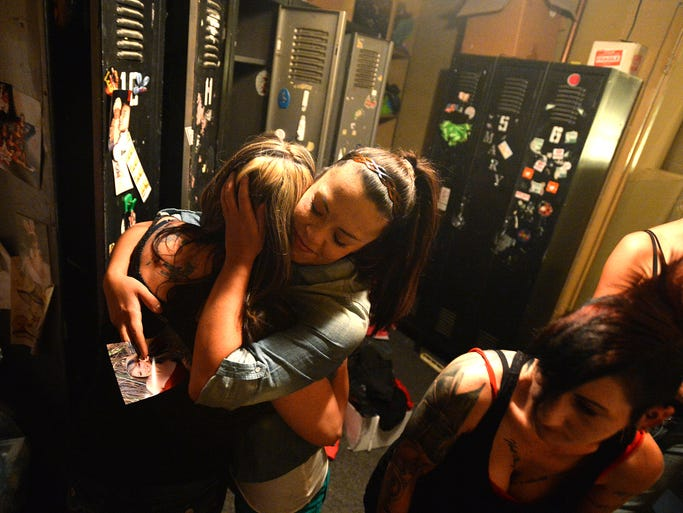 Miriah Woody, center, who has been a dancer at A Hunt Club for 9 years, embraces Deb Alexander, left, who was an employee for 22 years as they and other women remove their personal items from lockers in a dressing room of the Fort Collins gentlemen's club on Sunday, Sept. 8, 2013. The women learned early Sunday morning that the establishment had been sold and that they no longer had jobs. Timberline Church plans to buy the building and open a new church in that location.