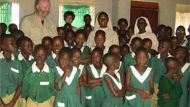 Chris Hoar, founder and director of CARITAS for Children, with Little Sisters of Saint Francis and student in Uganda.