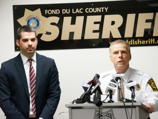 Prosecuting attorney Eric Toney stands to Sheriff Mick