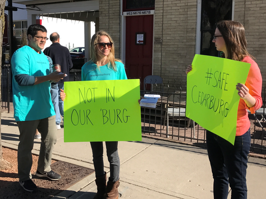 (from left): Antonio Ramirez, Charlotte Giuffre, and Kate McCormick of the Committee for a Safe Cedarburg protest outside the August Weber Haus during Winter Fest on Saturday, Feb. 18.