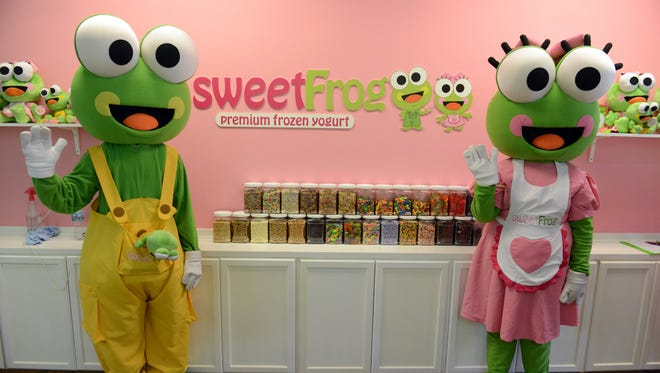 The sweetFrog mascots pose in a store in this file photo.