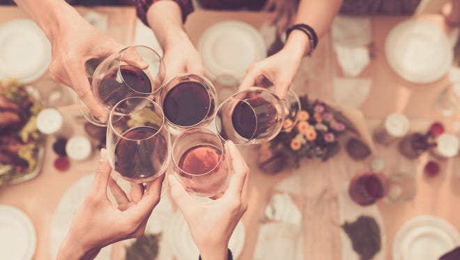 Friends clink wine glasses around a dinner table.